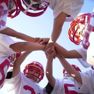 kids in football team huddle