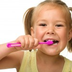little girl in pigtails brushing her teeth